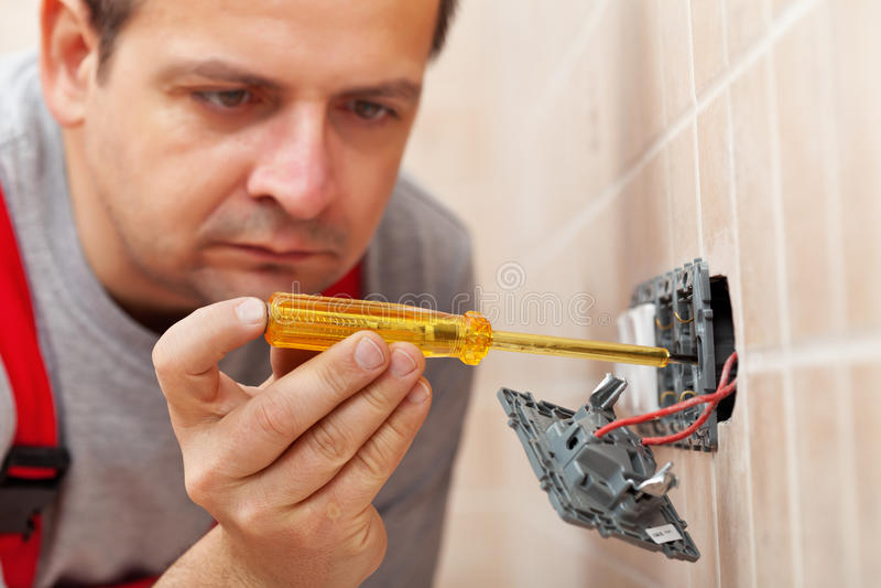 Elektriker som kontrollerar väggfasta tillbehöret med spänningstesteren arkivbild