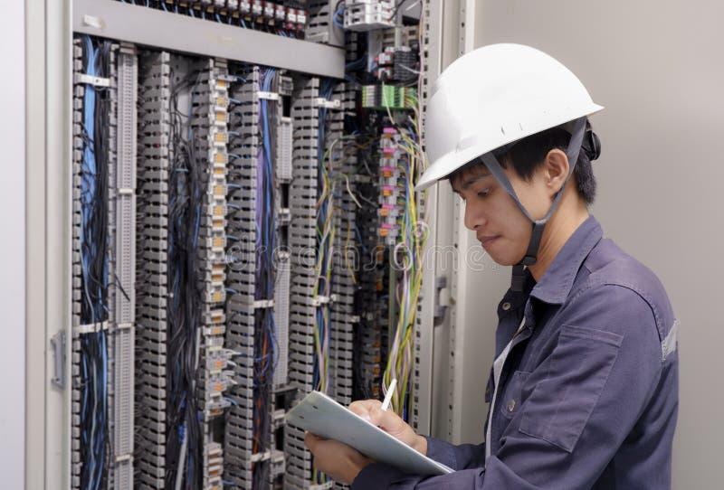 Elektriker som ler och att kontrollera elektriska askar i den industriella fabriken royaltyfri fotografi