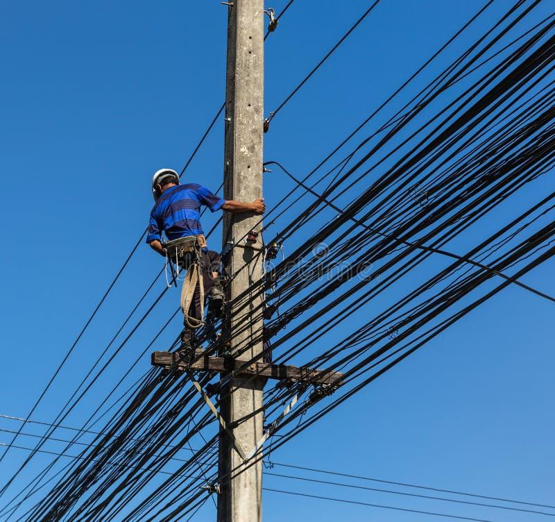 Elektriker som reparerar tråd av kraftledningen royaltyfri bild