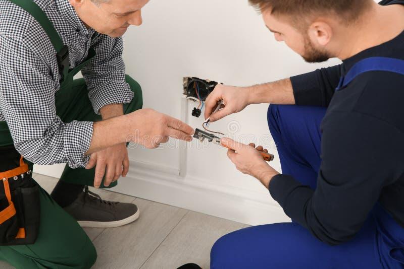 Elektriker und Lehrling, die mit Drähten arbeiten lizenzfreies stockbild