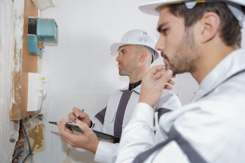 Elektrikerarbeitskräfte, die Spannungssicherungsbrett überprüfen lizenzfreies stockfoto