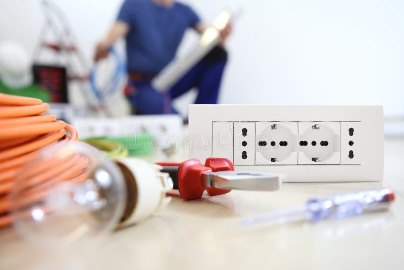 Elektrikerarbete med elektrisk utrustning i förgrunden, kulan, hjälpmedlen och håligheten, elektriska strömkretsar, elektriskt le arkivfoton