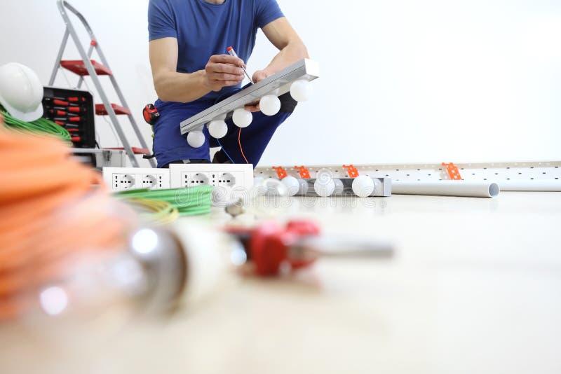 Elektrikerarbeten med skruvmejsel installerar lamporna, elektriska strömkretsar för huset, elektriskt ledningsnät arkivbild