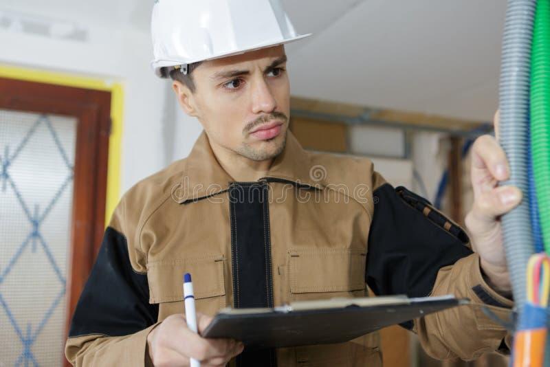 Elektrikerbyggmästareteknikern kontrollerar kabelledningsnät på den inomhus konstruktionsplatsen arkivfoto