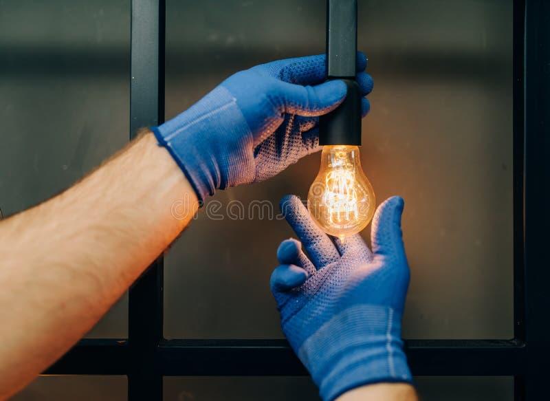 Elektrikeren ändrar den ljusa kulan, faktotum royaltyfri bild