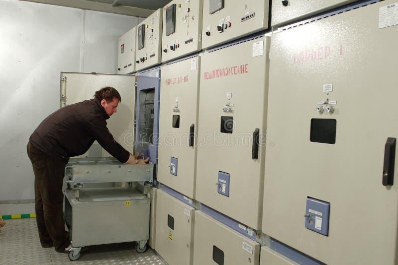 Elektrikeren ger underhåll av den elektriska panelen i switchbo royaltyfria foton