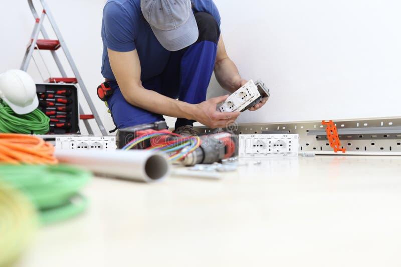 Elektrikeren på arbete med håligheten, installerar elektriska strömkretsar, elektriskt ledningsnät arkivbild