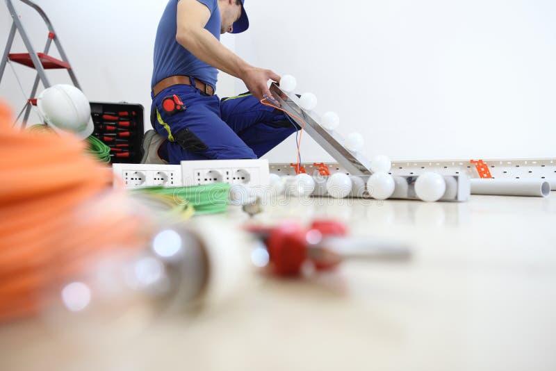 Elektrikeren på arbete som installerar lampan, installerar elektriska strömkretsar, elektriskt ledningsnät royaltyfri foto