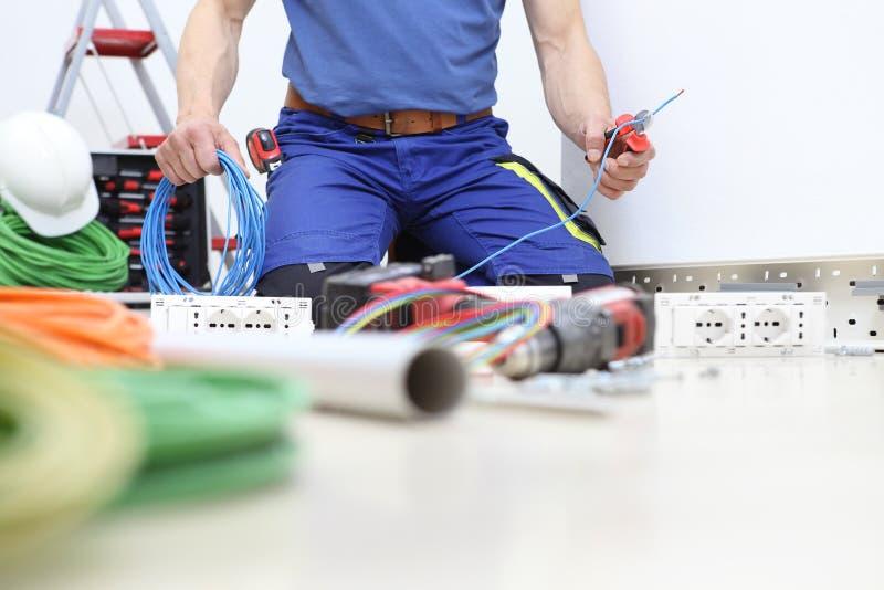 Elektrikeren p? arbete med pojkar i hand klippte den elektriska kabeln, installerar elektriska str?mkretsar, elektriskt ledningsn fotografering för bildbyråer