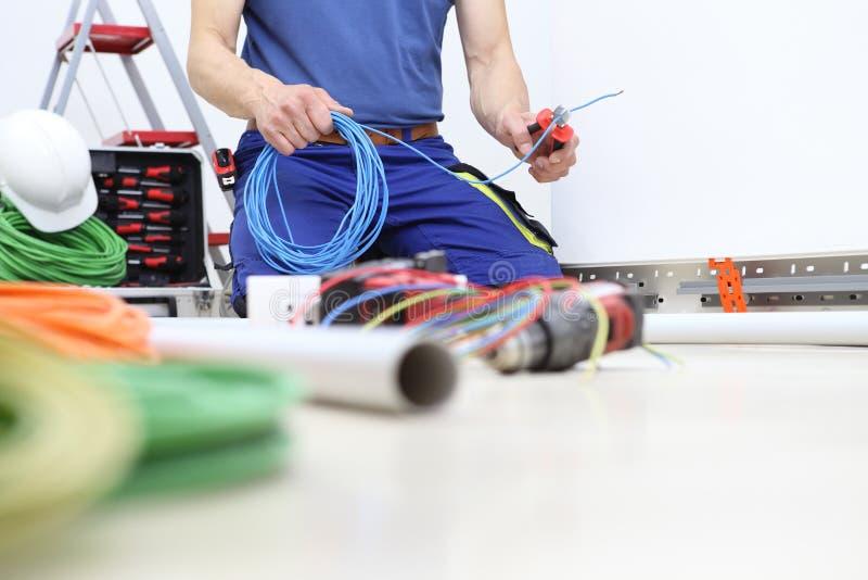 Elektrikeren p? arbete med pojkar i hand klippte den elektriska kabeln, installerar elektriska str?mkretsar f?r elektriskt lednin arkivfoto