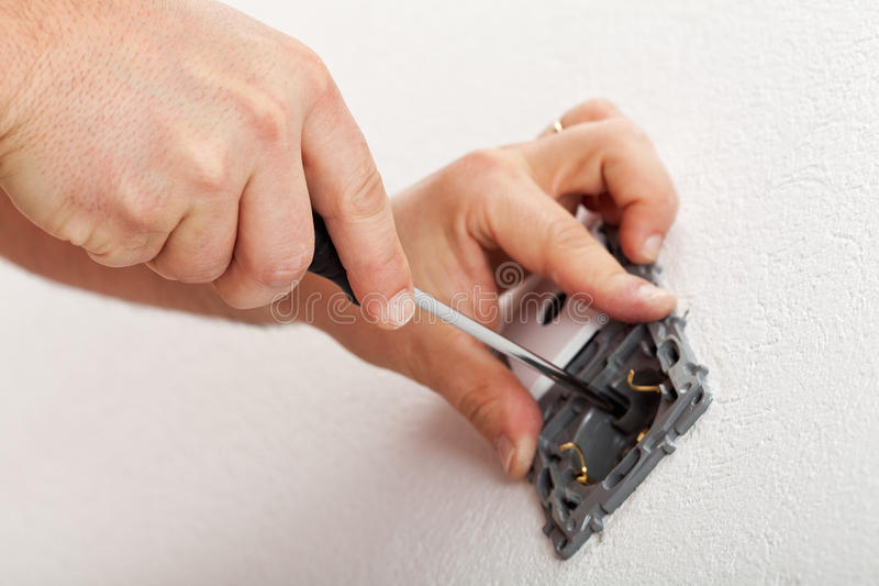 Elektrikeren räcker montering av det elektriska väggfasta tillbehöret arkivfoto