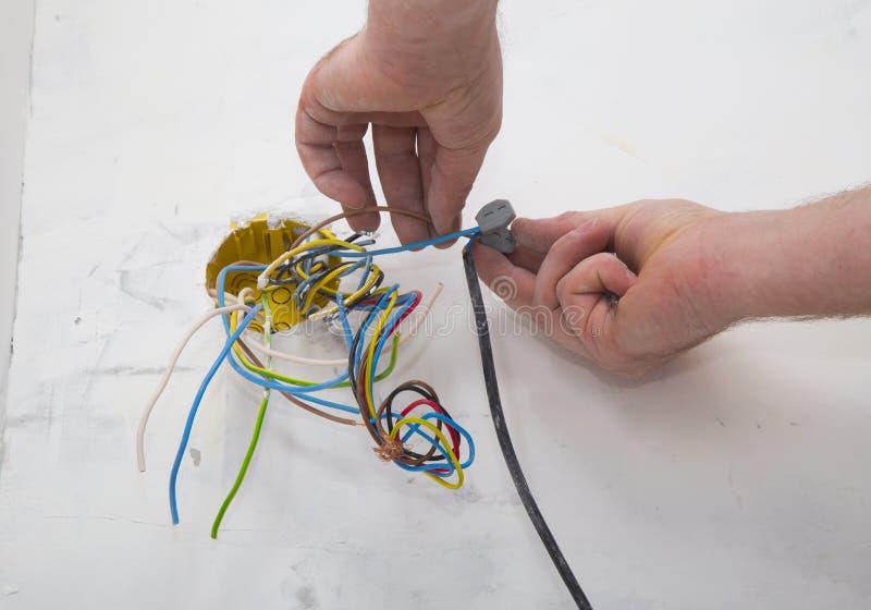 Elektrikerhänder som installerar ledningsnät royaltyfria foton