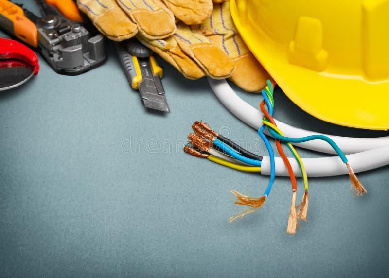 Elektrikerhandskar och hjälpmedel på träbakgrund arkivbild