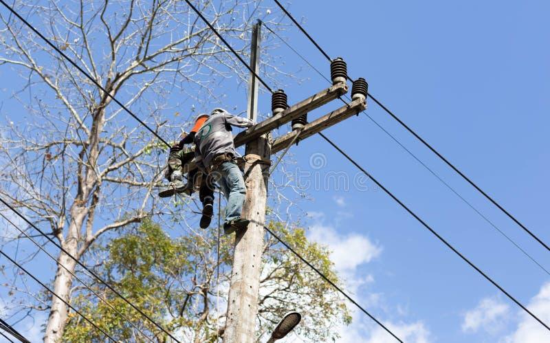 Elektrikerlinjearbetare som reparerar arbete på elkraft arkivfoton