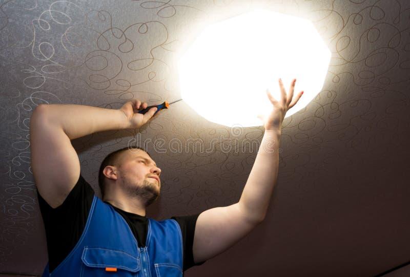 Elektrikermannen som arbetar på yttre ljus, installerar den LEDDE utbyteslampan hemma Under konstruktion arkivfoto
