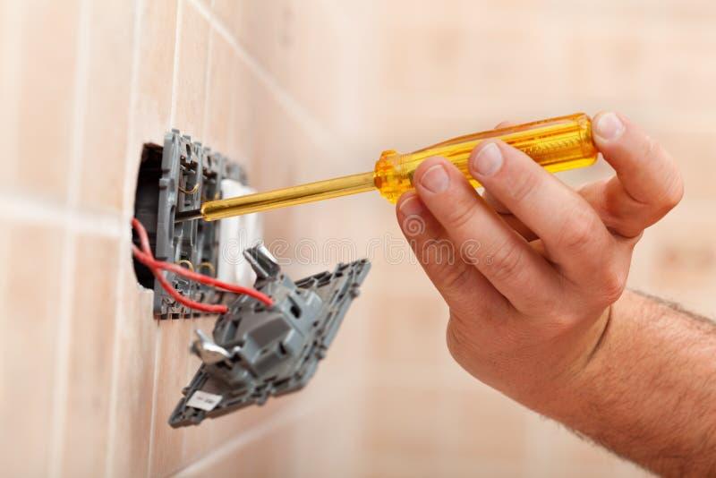 Elektrikerprüfung für Strom in der elektrischen Wandbefestigung stockfoto