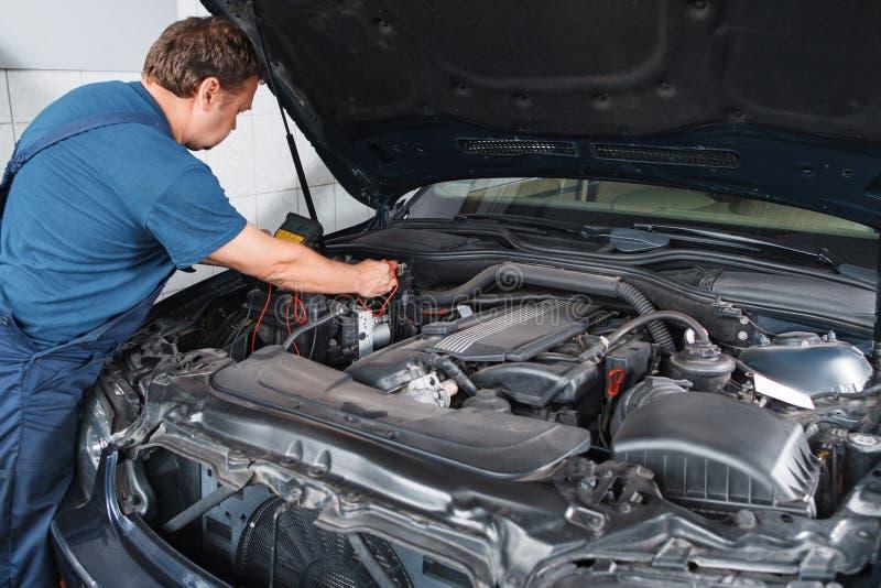 Elektrikerprüfungsauto mit Vielfachmessgerät an der Garage lizenzfreies stockbild