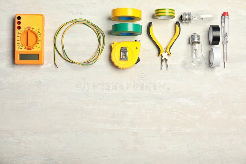 Elektrikers hjälpmedel och utrymme för text på ljus bakgrund arkivfoto