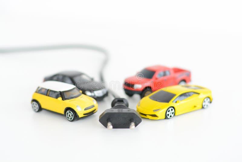 Elektrisch auto'sconcept met vele speelgoedvoertuigen op witte achtergrond stock foto's