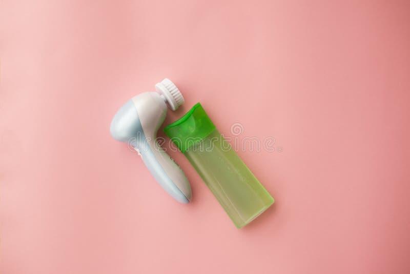 Elektrisch borstelreinigingsmiddel en gel voor het reinigen van het gezicht op een roze achtergrond Gezichts zorg Kosmetisch appa stock foto's