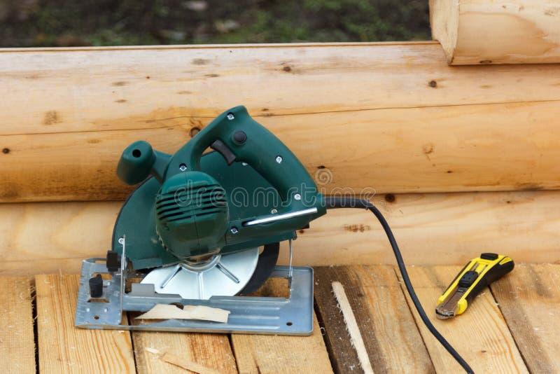 Elektrisch cirkelzaag en mes op een houten platform stock foto