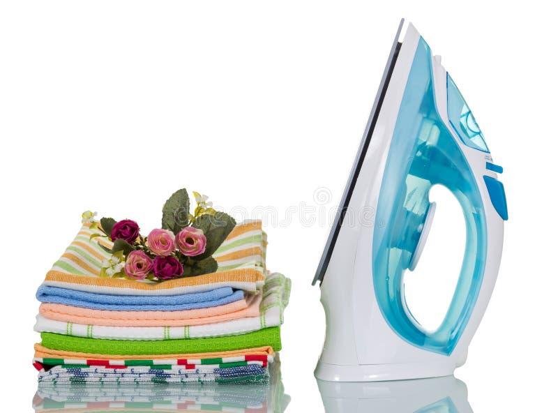 Elektrisch ijzer en gestreken die stapel keukenhanddoeken op wit worden geïsoleerd stock fotografie