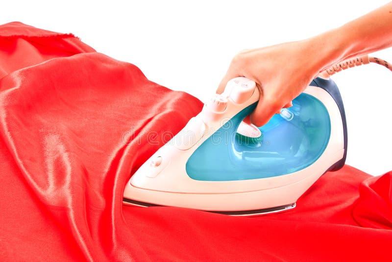 Elektrisch ijzer op rode geïsoleerde= doek royalty-vrije stock foto