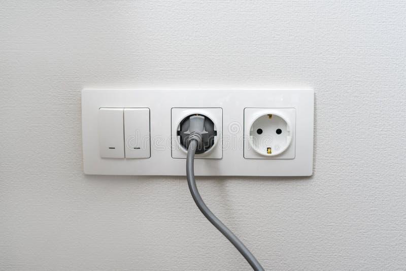 Elektrisch lichtschakelaar en contactdoos op de lege muur, elektro geschakelde machtscontactdoos en stop Het concept energie - be royalty-vrije stock afbeelding