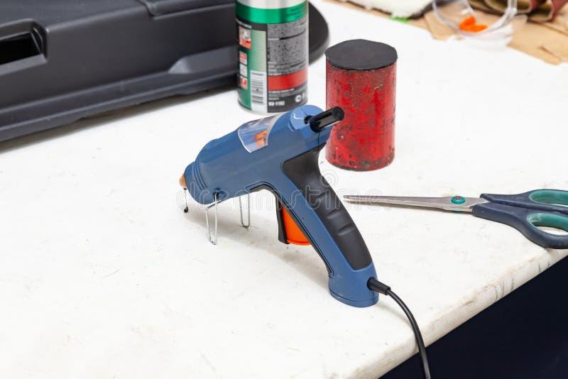 Elektrisch lijmkanon voor het drukken van blauwe lijm op de werkbank voor handwerk in de workshop naast schaar en wegende agent v royalty-vrije stock afbeelding