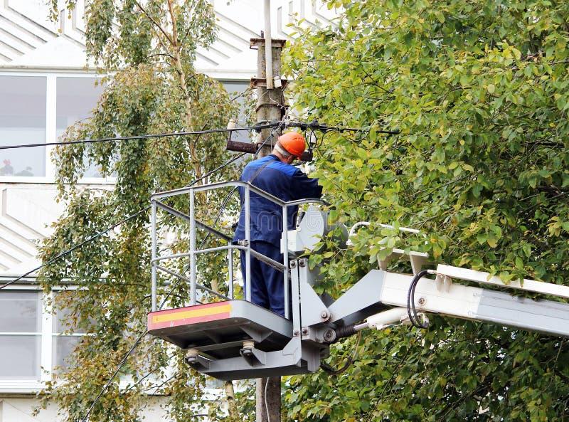 Elektrische Arbeitskraft, welche die Drähte auf dem Pfosten mithilfe des Aufzugautos repariert stockfoto