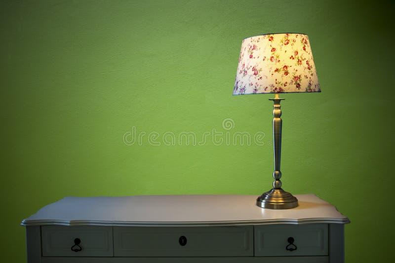 Elektrische Beleuchtungslampe auf weißer Tabelle mit Smaragdgrün-Zementwandhintergrund stockbilder