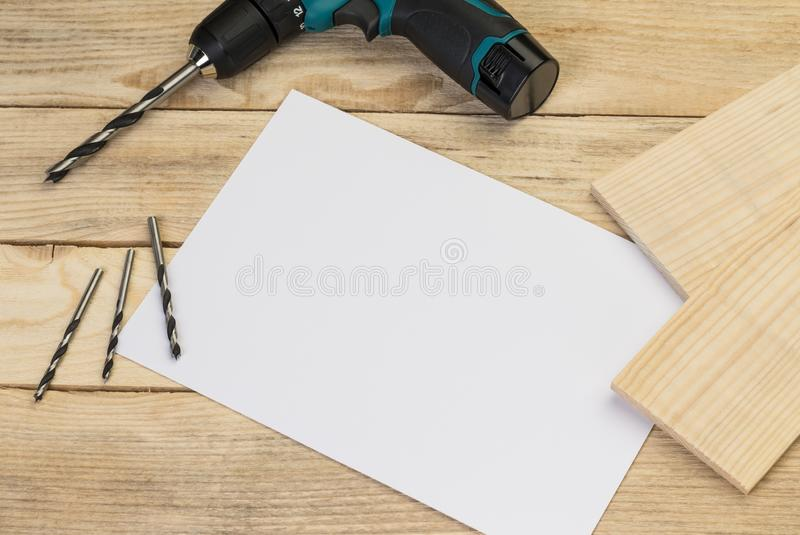 Elektrische Bohrmaschine und Stückchen auf einem hölzernen Hintergrund stockbilder
