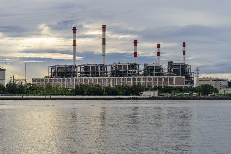 Elektrische centrale bij rivieroever tijdens zonsopgang stock foto