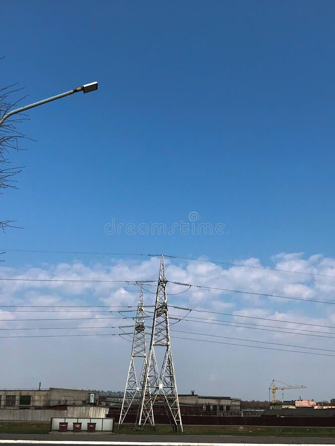 Elektrische centrale met hoge metaaltorens en draden met hoog voltage, pijlers tegen de achtergrond van industriële gebouwen royalty-vrije stock foto