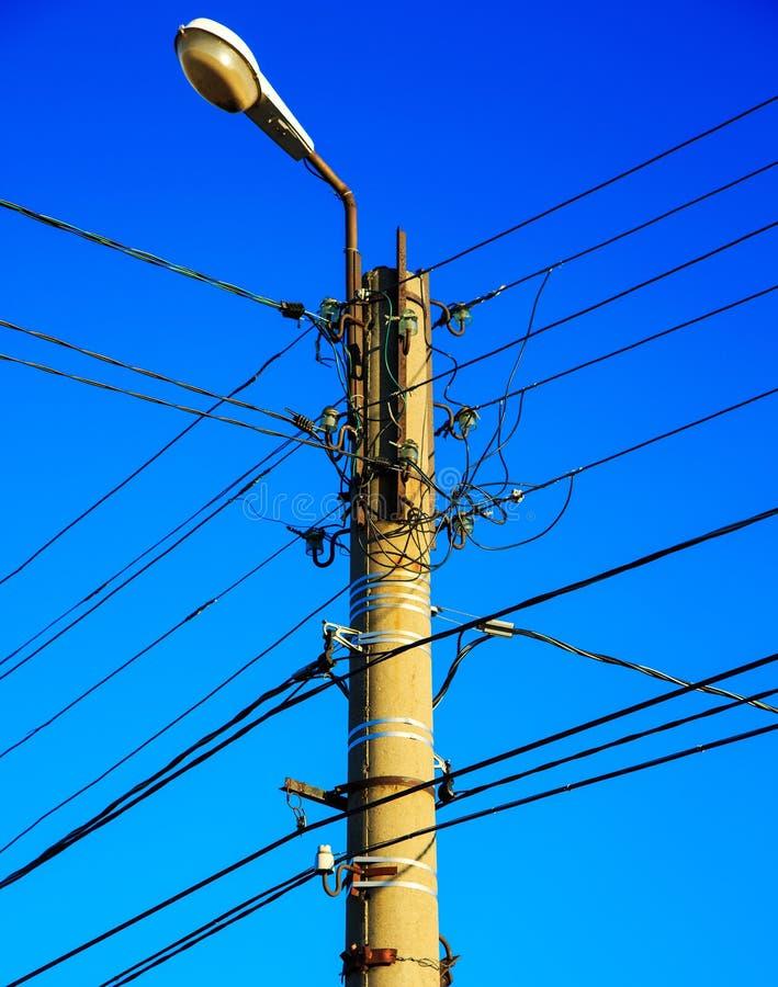 Elektrische draad en lamp op elektropool met blauwe bewolkte hemelachtergrond stock foto
