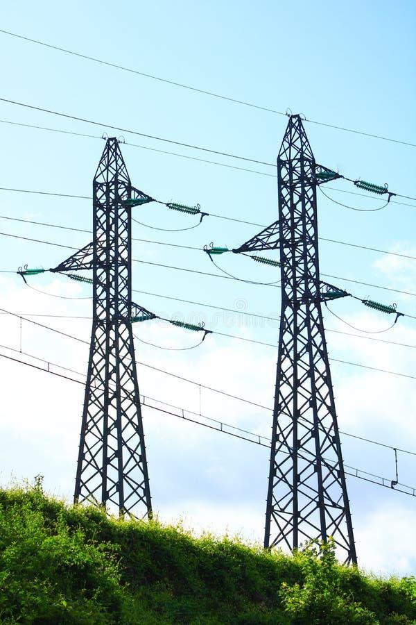 Elektrische draden bij de bovenkant van metaaltorens die de stad voedt stock foto