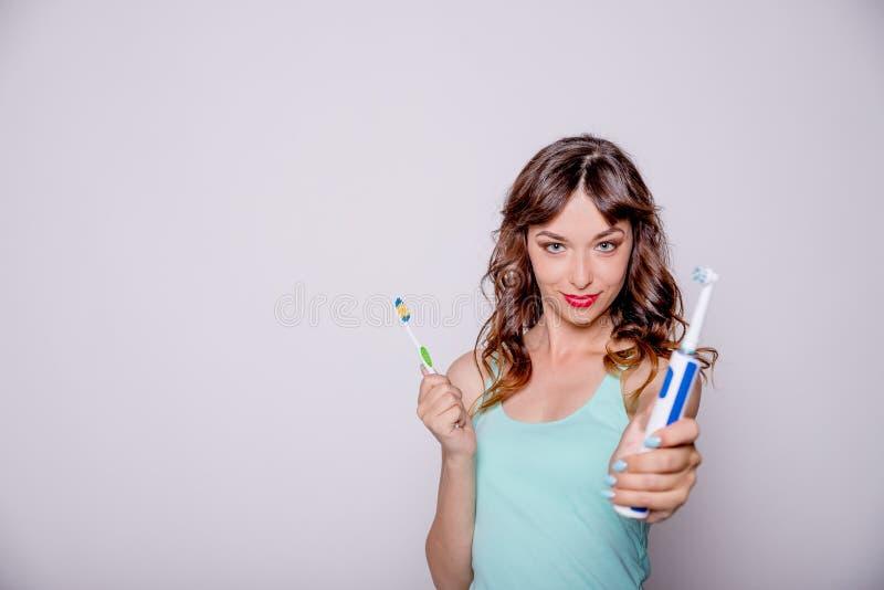 Elektrische en traditionele tandenborstel Hygiëne van de mondholte Een jonge mooie vrouw kiest tussen elektrisch en royalty-vrije stock foto's