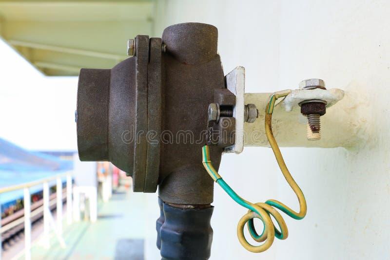 Elektrische Erdungen herein angeschlossen an Wand des geschliffenen Stahls lizenzfreies stockfoto