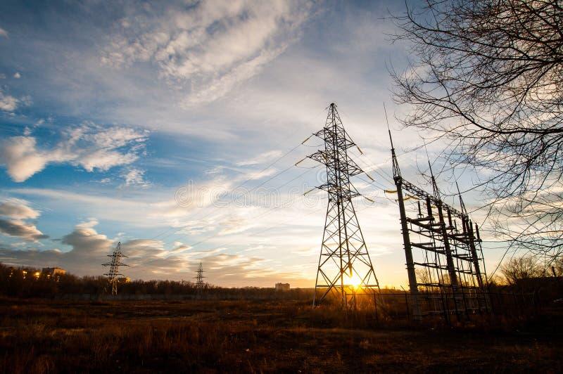 Elektrische Fernleitungen auf dem Gebiet nahe der Stadt in den Strahlen eines schönen hellen Sonnenuntergangs stockbilder