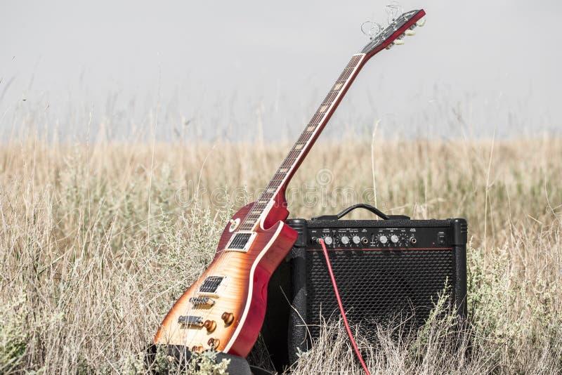 Elektrische gitaar en ampère op het gebied, het concept muziek royalty-vrije stock foto's