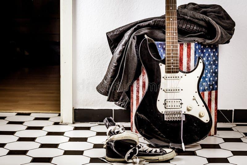Elektrische gitaar, leerjasje en sportenschoenen stock afbeeldingen