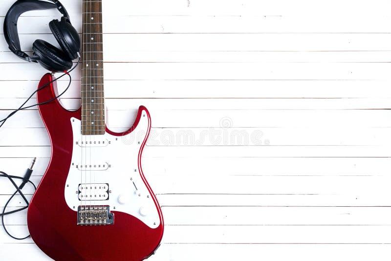 Elektrische gitaar met hoofdtelefoons op witte houten lijst Exemplaar Spac royalty-vrije stock foto