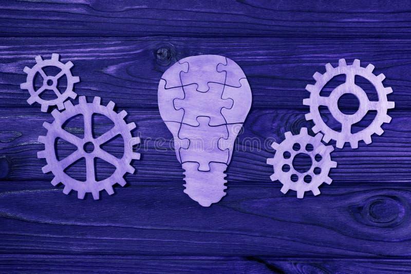Elektrische Glühlampe von den Puzzlespielen mit Gängen auf einem hölzernen Hintergrund stockbilder