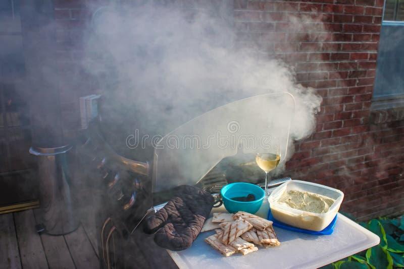 Elektrische grill op het dek met veel rook ontwikkeling - frybread en onderdompeling en een glas witte wijn op scherpe raad stock fotografie