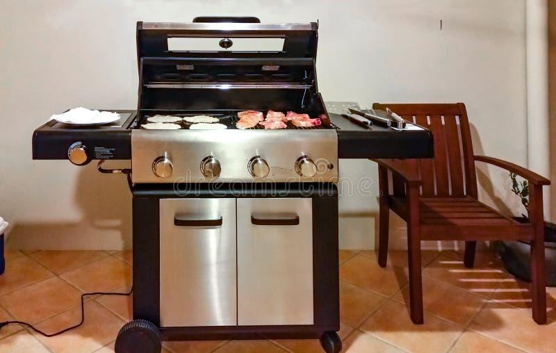 Elektrische grill op tegelterras tegen gipspleistermuur met vlees en flatbread en kokende hulpmiddelen klaar te gaan royalty-vrije stock afbeeldingen