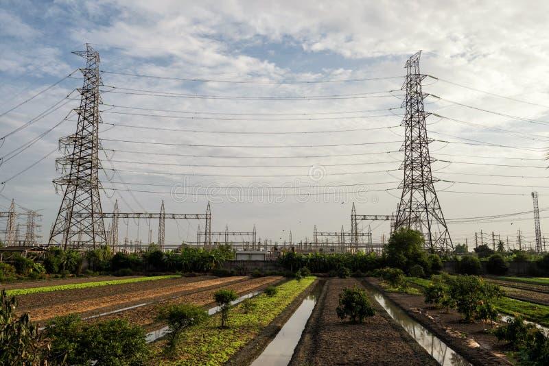 Elektrische hoogspanningspolen dichtbij landbouwbedrijf stock afbeeldingen