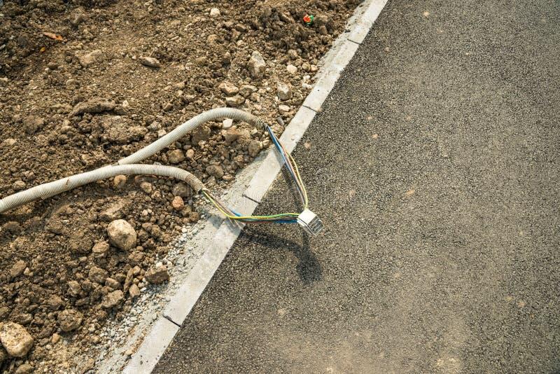 Elektrische Kabel auf Bürgersteig nahe Baustelle stockfotos