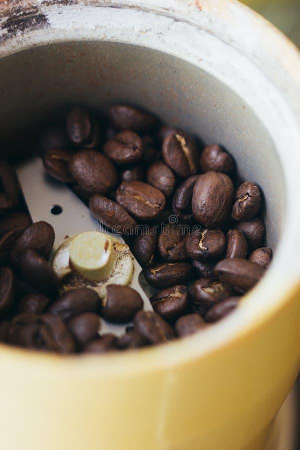 Elektrische Kaffeemühlemaschine mit Kaffeebohnen nach innen Kaffeemühle über dem Küchentisch stockfotografie