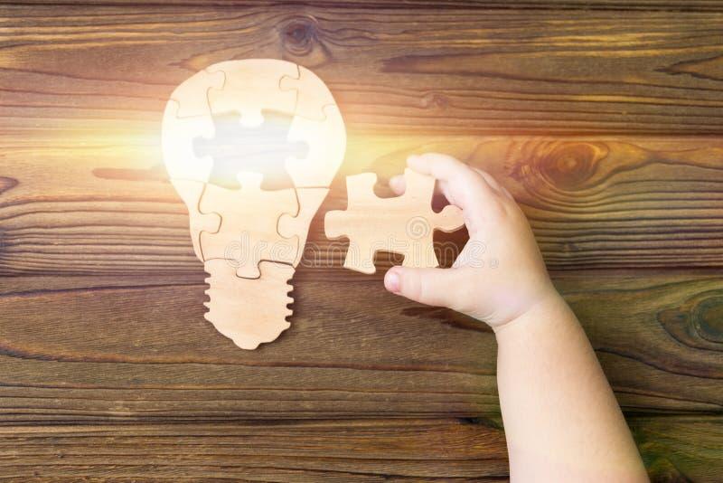 Elektrische Lampe von den Puzzlespielen, eine Kinderhand auf einem Holztischhintergrund stockbild