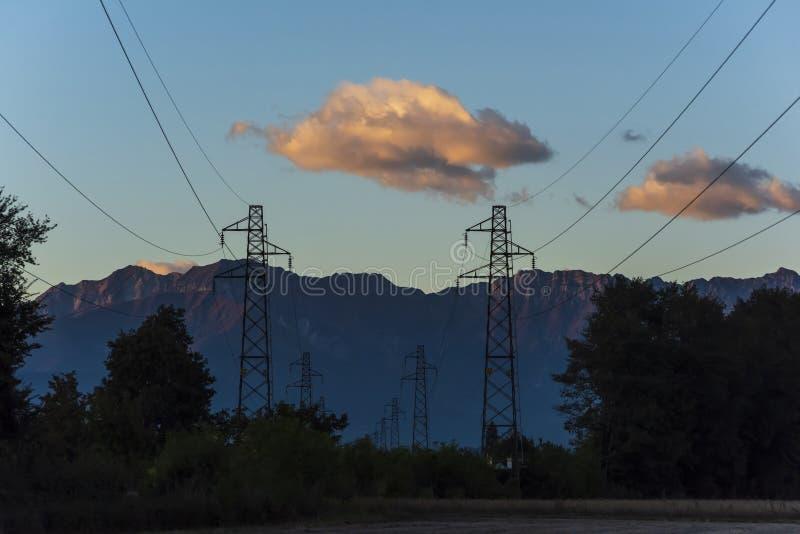 Elektrische Linien an der Dämmerung mit Bergen im Hintergrund stockfoto